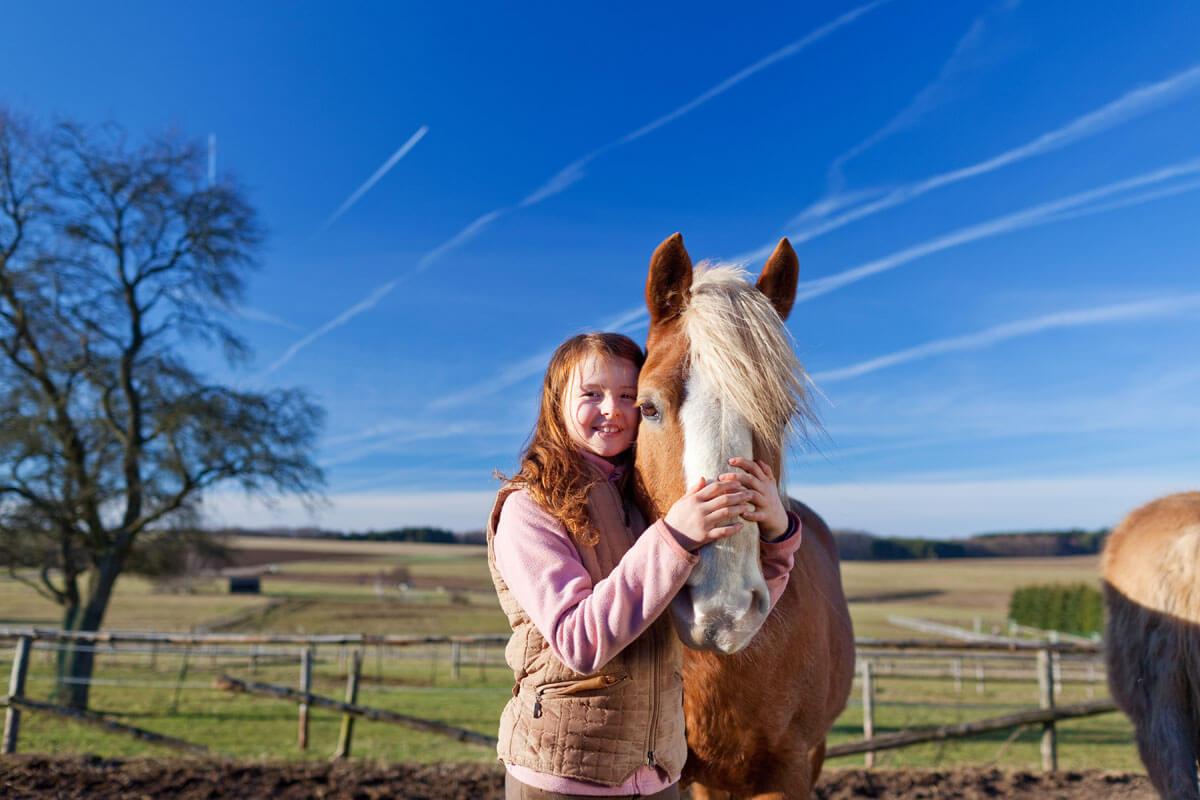 Mädchen mit ihrem Lieblingspferd - Ein Kindertraum: Herbstferien auf dem Reiterhof