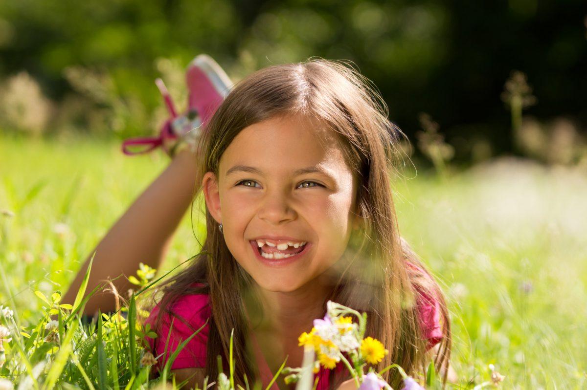 Lachendes Mädchen auf einer Frühlingswiese