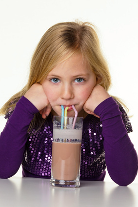 Ein kleines Kind trinkt heisse Schokolade