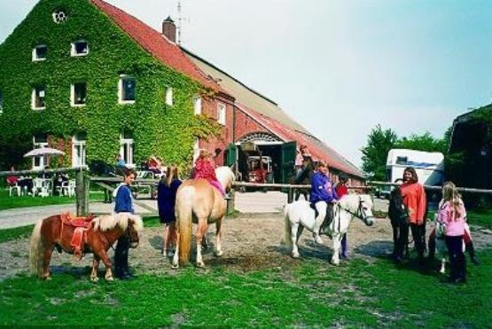 Hofansicht mit Pferden und Reitern