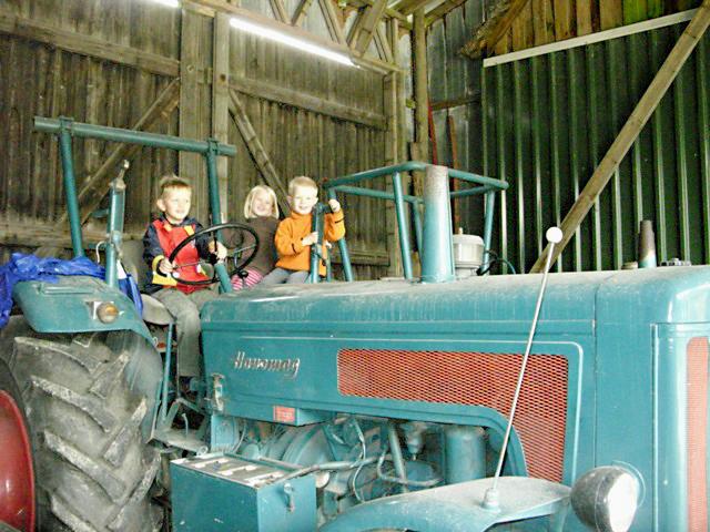 Kinder auf einem alten Traktor am Liethshof